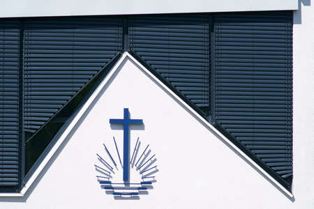 Lowered blinds on a newly built and modern church with a cross symbol with rays. Stock fotó