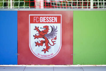 Giessen, Germany - August 13, 2019: The coat of arms of the football club FC Giessen at the band of the Waldstadion at a game of the regional league on 13 August 2019 in Giessen. 新聞圖片
