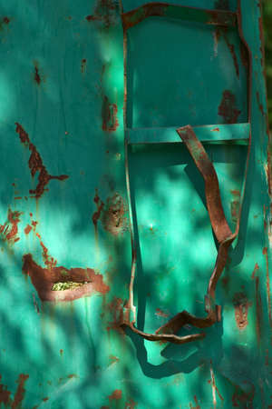 The bent ladder of a rusted container.