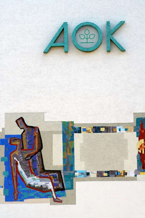 Alzenau, Germany - August 24, 2019: The logo of the health insurance company AOK on the facade of an office and commercial building with a mosaic painting on August 24, 2019 in Alzenau.