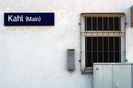 The wall of the station building of the city Kahl with a sign and barred window. Banco de Imagens