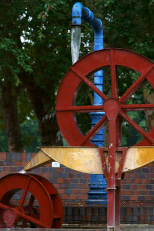 The sculpture of a mill wheel which is driven by water.