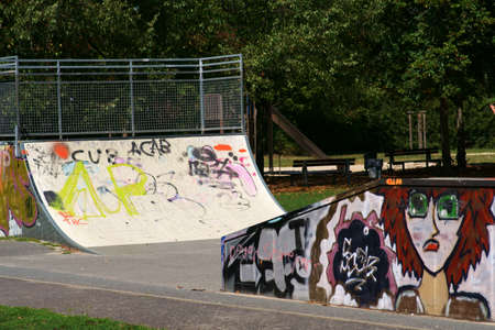 Walldorf, Germany - August 11, 2019: The skate tracks of a youth and sports park on the edge of a park landscape with graffiti on August 11, 2019 in Walldorf. 新聞圖片