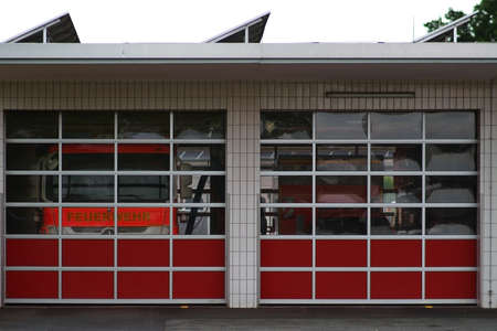 Two fire engines are behind the Plexiglas panes of a garage of the fire department.