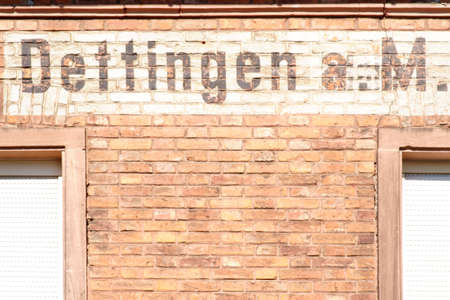 The name Dettingen at the brick facade of an old building. Banco de Imagens