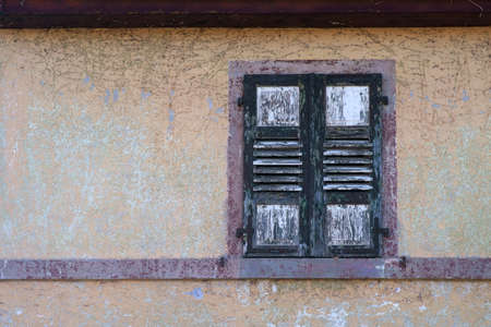 A rotten and dilapidated shutter of a window on a bleached facade.  Banco de Imagens