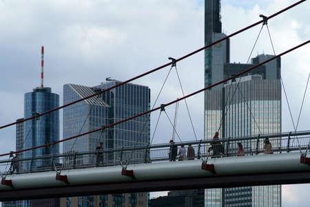 Frankfurt, Germany - August 03, 2019: Pedestrians walk across the modern bridge on August 03, 2019 in Frankfurt.