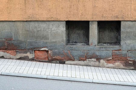 An old residential building with cellar windows on a walkway with slope.   Banco de Imagens
