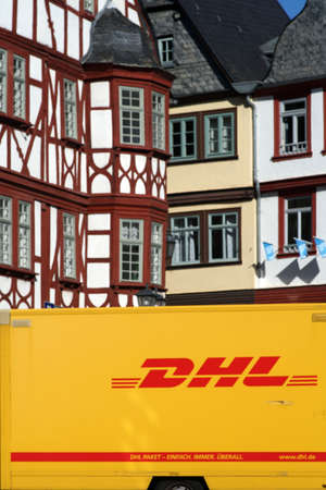 Limburg, Germany - October 12, 2019: A parcel of DHL parcel service stands in front of half-timbered houses of the listed Old Town on October 12, 2019 in Limburg.