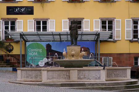 Homburg, Germany - October 19, 2019: The fountain on the market square in front of a historic building and cafe on October 19, 2019 in Homburg.