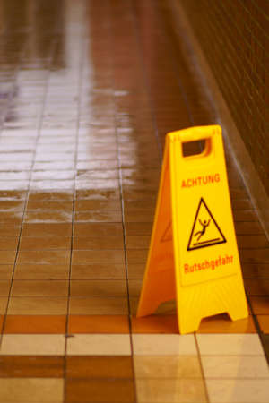 The wet tiles and clinker of a freshly wiped tunnel floor with a warning sign: Caution Slipping hazard! Banco de Imagens