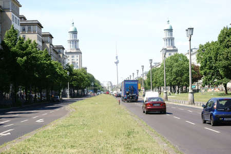 Berlin, Germany - May 09, 2016: Road traffic along the Karl-Marx-Allee with the towers of the Frankfurt gate in the district Friedrichshain on May 09, 2016 in Berlin.
