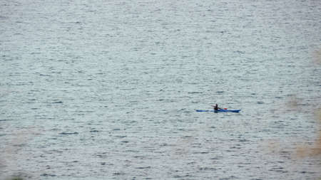 Man in row boat at open sea