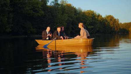 Officeworkers are in a boat, having a conversation