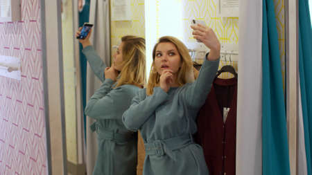 Nice girl makes a selfie on her phone in the fitting room