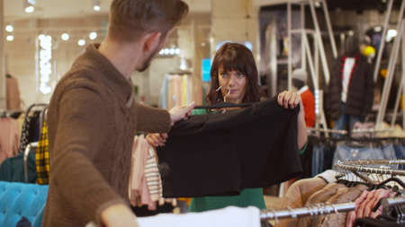 Man offers his woman a sweater and shorts in a store Banco de Imagens - 133698816
