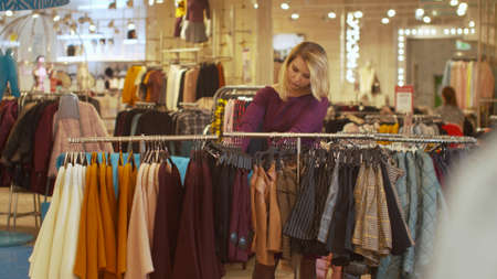 Woman sorts things out on a hanger in a store