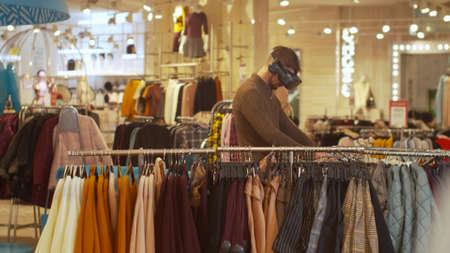 Man walks around the store wearing virtual reality glasses Banco de Imagens - 133698825