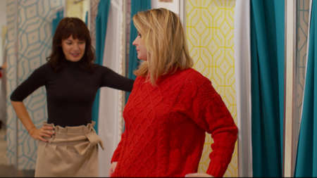 Friends in the fitting room, one girl tries on a sweater