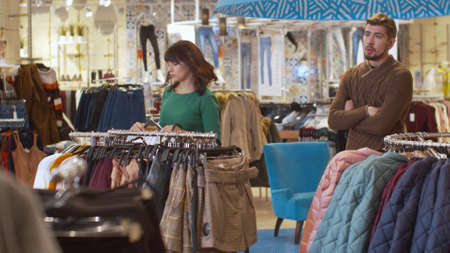 Pretty woman chooses clothes, guy sighs heavily