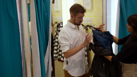 Woman gives her man clothes in the fitting room Banco de Imagens - 133698861