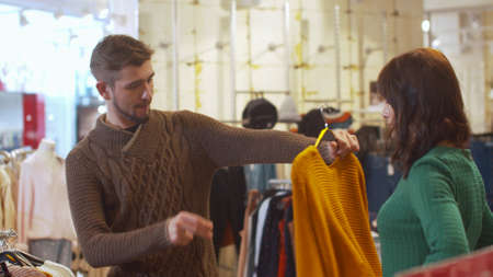 Young man chooses clothes for his woman