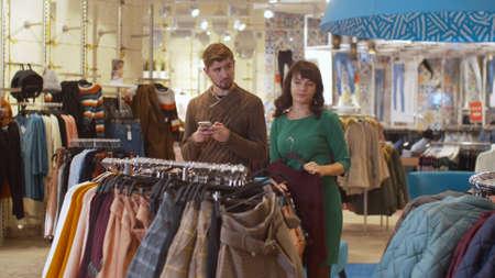 Girl shows her boyfriend the clothes she has chosen