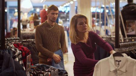 Beautiful woman chooses her man a shirt in a store Banco de Imagens