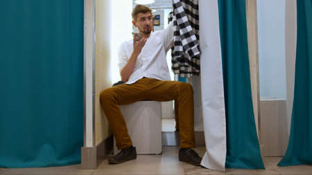 Man records a voice message in the fitting room