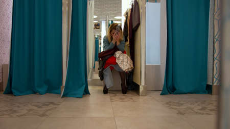 Girl sits in the fitting room with a bunch of clothes Banco de Imagens - 133698905