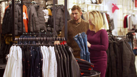 Girl helps to choose clothes for her boyfriend in the store