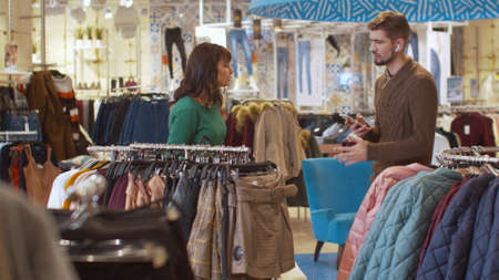 Nervous woman and her man in a clothing store Banco de Imagens