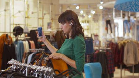 Woman talks via video in headphones and shows clothes to the interlocutor Banco de Imagens - 133698917