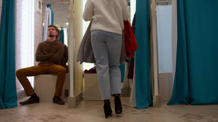 Girl chooses a sweater in the fitting room Banco de Imagens - 133698915