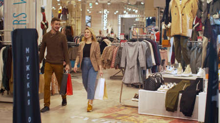 Happy couple walk in a store with packages Banco de Imagens