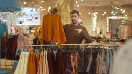 Young man takes sweater and shorts from the hanger