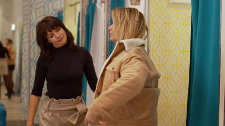 Friends in the fitting room, one girl tries on a jacket