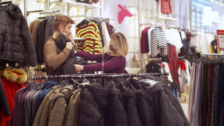 Young woman helps her man to choose a jacket