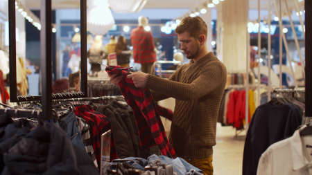 Young man is looking for clothes in a store Banco de Imagens