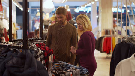 Pretty woman helps her man to choose a shirt