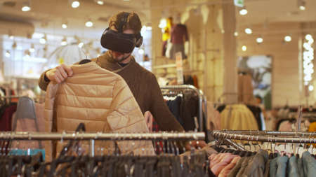 Man in virtual reality glasses chooses clothes Banco de Imagens - 133698959