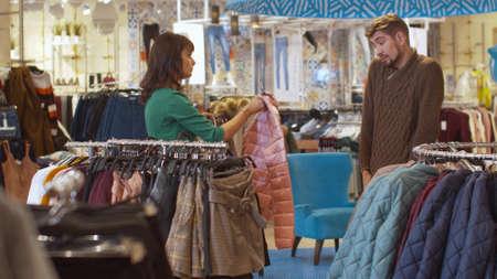 Woman chooses clothes, man wants to leave Banco de Imagens