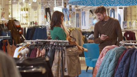 Young woman and her man in the clothing store