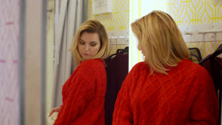 Pretty girl tryes on clothes in a fitting room Banco de Imagens