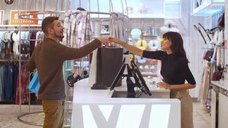 Girl gives a shopping bag to a man with smile Banco de Imagens - 133698986