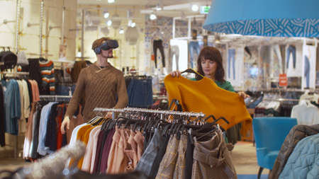 Guy in virtual glasses, girl chooses things and gets angry Banco de Imagens