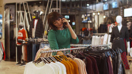 Nice woman choses a sweater and talks on the phone rapturously Banco de Imagens - 133698996