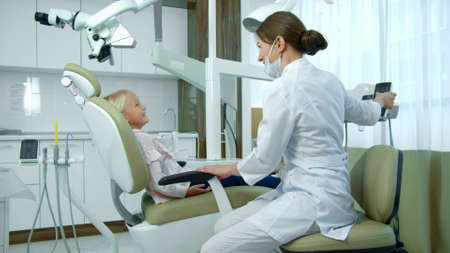 Doctor regulates the chair where little patient is sitting. Banco de Imagens