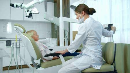 Zahnarzt rückt Stuhl zurück, kleines Mädchen sitzt.
