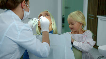 Dentist looks at womans teeth, daughter sits with her